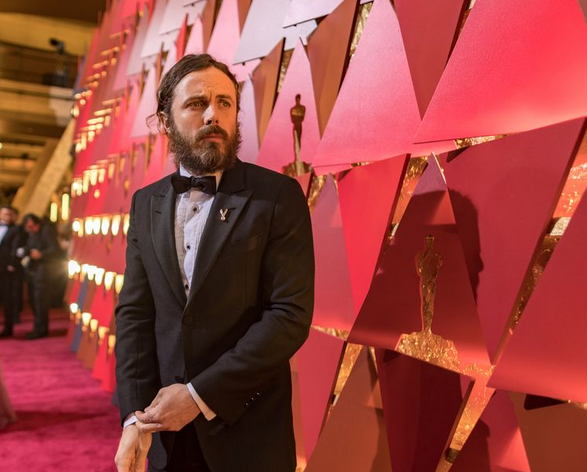 Casey Affleck stands on the red carpet looking confused