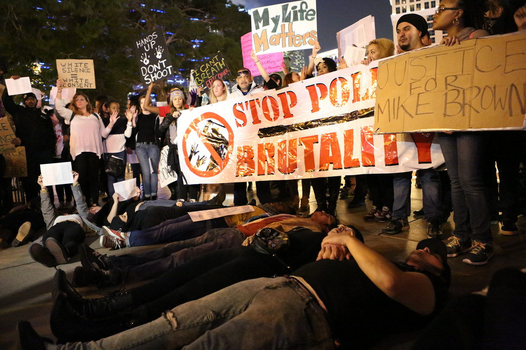 Protesters in Las Vegas hold us signs about police brutality.