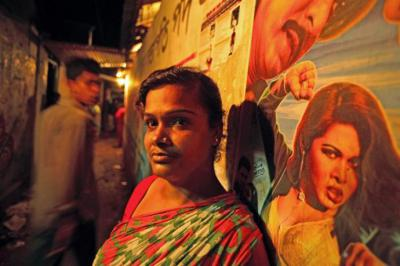 An image from Whore's Glory: A Bangladeshi woman stands outside, leaning against a wall on which is painted a woman from a movie or advertisement raising her fist as if mid-punch.