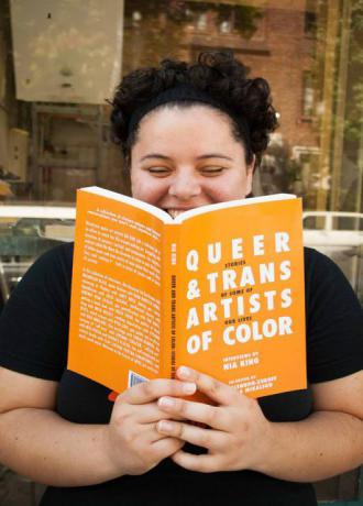 "someone reading a copy of ""queer and trans artists of color"""