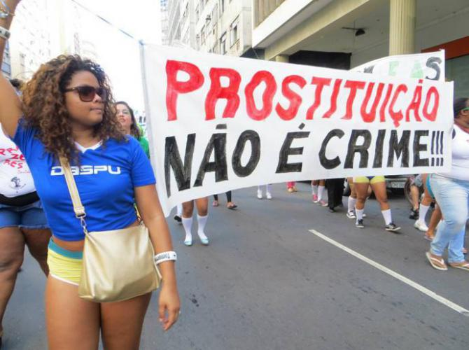 a protester wearing a world cup jersey holds a sign supporting sex workers