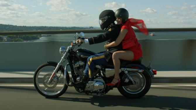 amira and sam ride a motorcycle, grinning