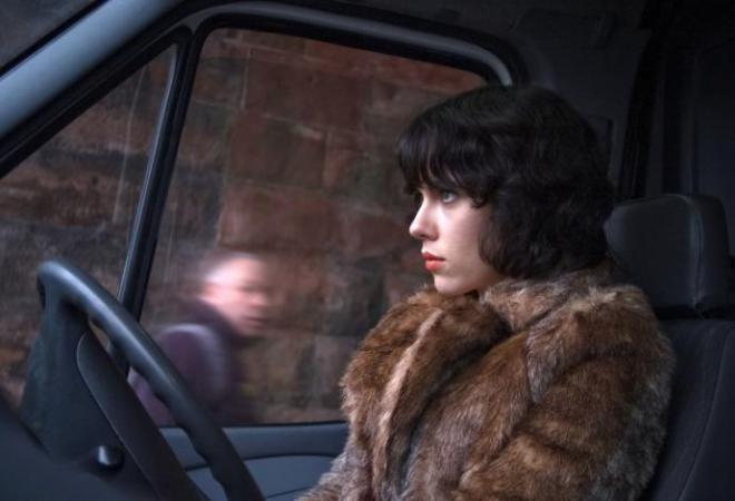 Johansson's character stares straight ahead from the driver seat of a van