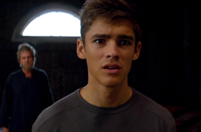 Brenton Thwaite stares at the camera in alarm in a scene from The GIver