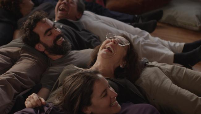 a still from Gloria, in which a group of people are laughing on the floor