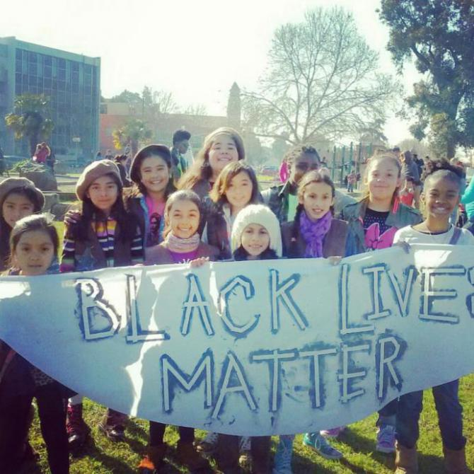 "the radical brownies holding a big protest sign that says ""black lives matter"""