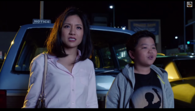 An Asian mom and her son stare at the screen in concern