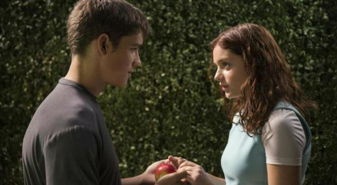 odeya rush and brenton thwaite stare at an apple in a scene from The Giver