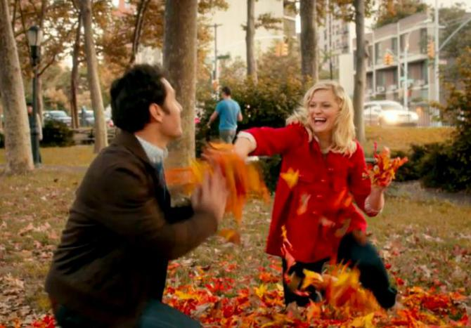 amy poehler and paul rudd whimsically throw leaves at each other