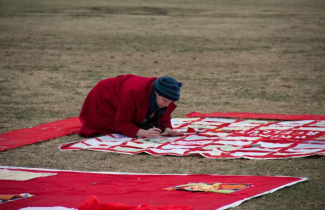 A person crouches over one of the red squares of the monument quilt