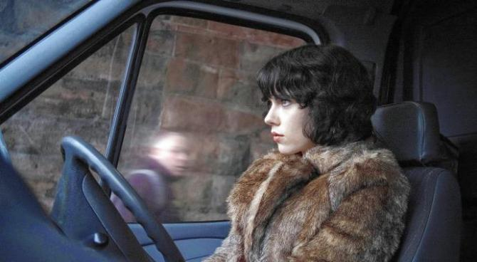"the alien in ""under the skin"" sitting in her van as a man walks past"