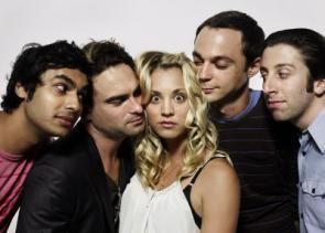 Cast of the Big Bang Theory: four men and one woman. The woman is facing the camera and the men are all facing the woman, who is in the center of the group