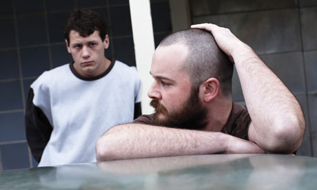 A still from the movie Snowtown of the two main protagonists and killers. They stand outside, one in profile touching his shaved head, the other in the background, looking forlornly at his partner.