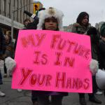 "A CHILD AT AN IDLE NO MORE PROTEST, HOLDING A SIGN READING ""MY FUTURE IS IN YOUR HANDS"""