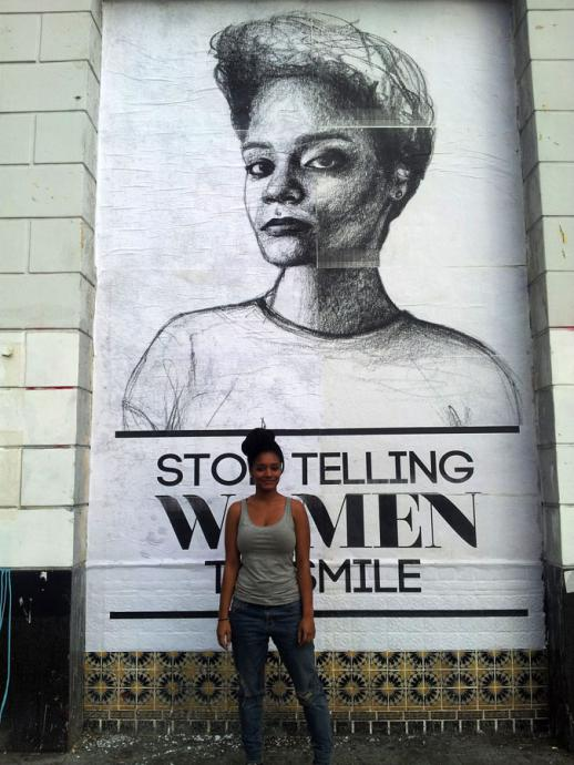 "The artist in front of a giant poster that says ""stop telling women to smile"""