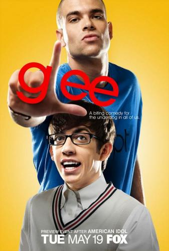 promotional poster for Glee, showing the upper torso of Artie, a white student with large glasses and a beige sweater. Standing behind him is another student, Puck, who is also white and wearing a blue tee shirt. Puck is making the 'loser' symbol with his hand placed in front of Artie's forehead, implying that Artie is a loser. Text reads: 'glee: a biting comedy for the underdog in all of us.' Image does not depict Artie's wheelchair, although this is a focal point of his character.