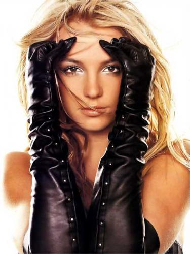 Britney Spears, white woman with blonde hair and brown eyes wearing elbow lengthed black leather gloves holding her face.