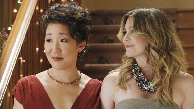 Meredith and Christina, shown from the chest up, at Christina's wedding. Christina is wearing a red gown and Meredith is in taupe with a large clunky necklace.