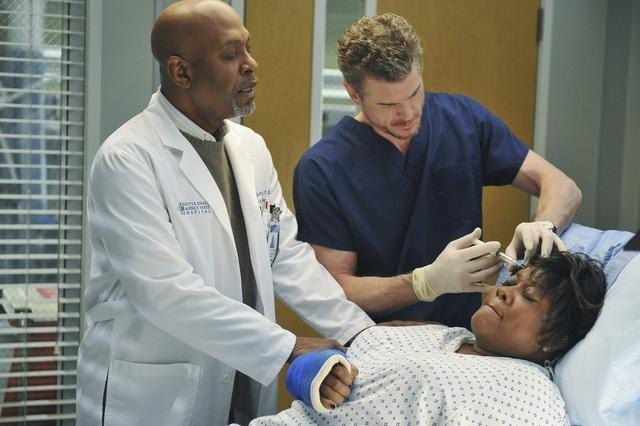 Adele in a hospital bed while Mark stitches her forehead and the Chief looks on.