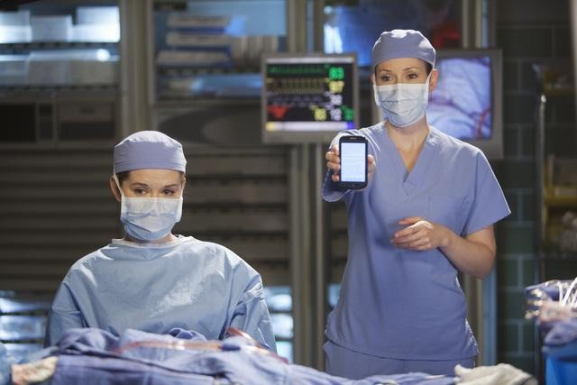 Meredith Grey, scrubbed in for surgery, holds up a smartphone she's been using to Tweet a surgery.