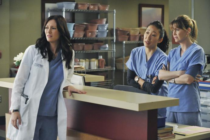 Meredith, Cristina, and Lexie at the nursing station, wearing skeptical expressions.