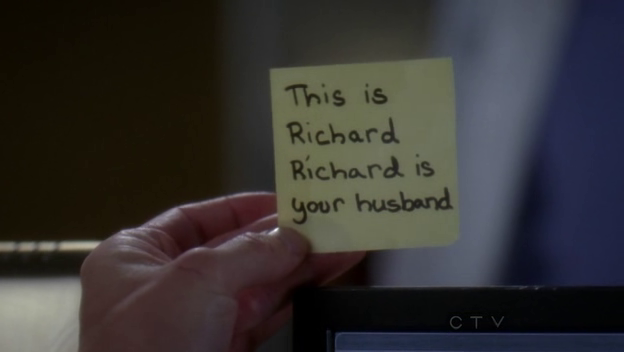 Meredith holds a postit reading: This is Richard. Richard is your husband.