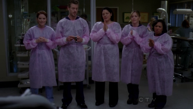 Kepner, Sloane, Torres, Robbins, and Bailey stand in pink gowns, applauding.