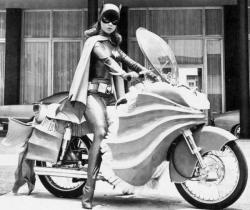 Yvonne Craig as Batgirl: she sits on a motorcycle and wears a cape and mask
