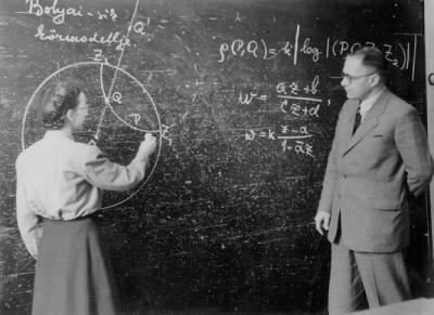 A black and white photograph of a woman writing a math equation on a chalkboard while a man looks on. They are both white and wearing professional attire.