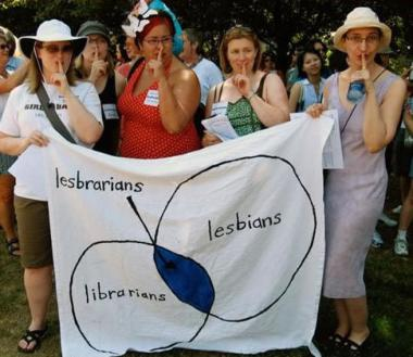 Lesbrarians Four women hold a lesbrarians banner at a march, holding their fingers in front of their lips in a shushing gesture